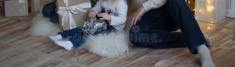 Mutter mit einem kleinen Kind nahe dem Baum des neuen Jahres sind dazu Geschenke und ein Kamin stockfotografie