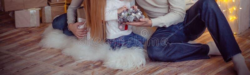 Mutter mit einem kleinen Kind nahe dem Baum des neuen Jahres sind dazu Geschenke und ein Kamin stockfotos