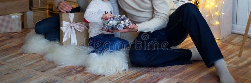 Mutter mit einem kleinen Kind nahe dem Baum des neuen Jahres sind dazu Geschenke und ein Kamin lizenzfreie stockfotos