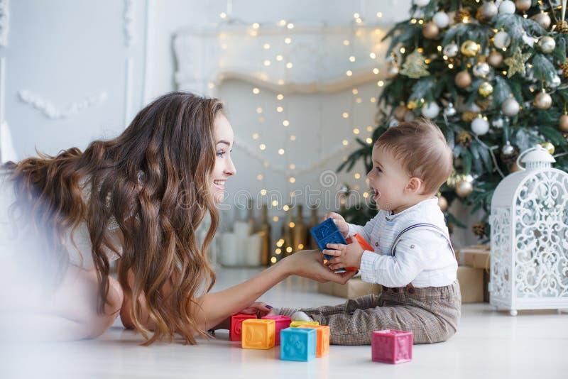 Mutter mit einem kleinen Sohn nahe einem schönen Baum in seinem Haus, das mit farbigen Würfeln spielt stockfoto