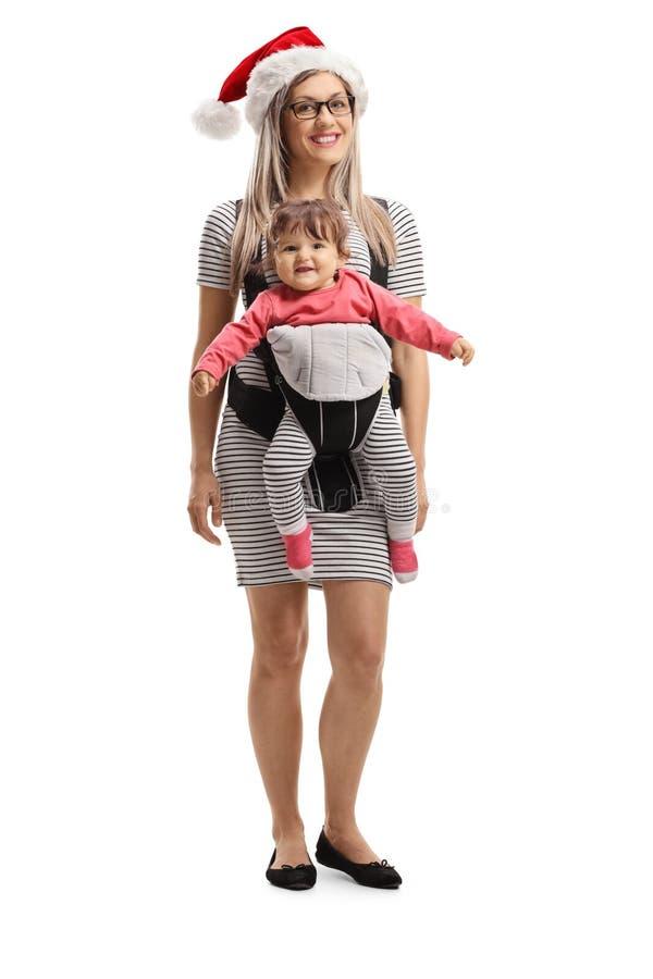 Mutter mit einem Weihnachtshut und einem Baby in einem Träger stockfotografie