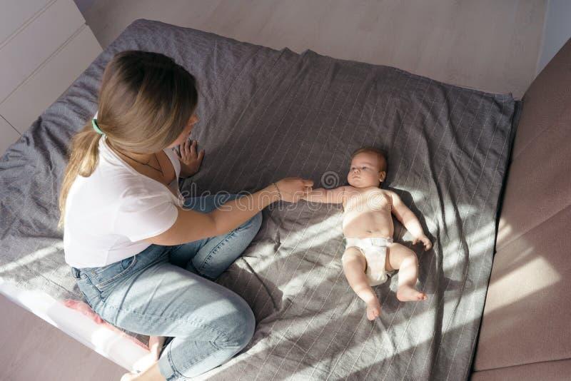 Mutter mit ihrem neugeborenen Sohn legen auf das Bett in den Strahlen des Sonnenlichts lizenzfreies stockfoto