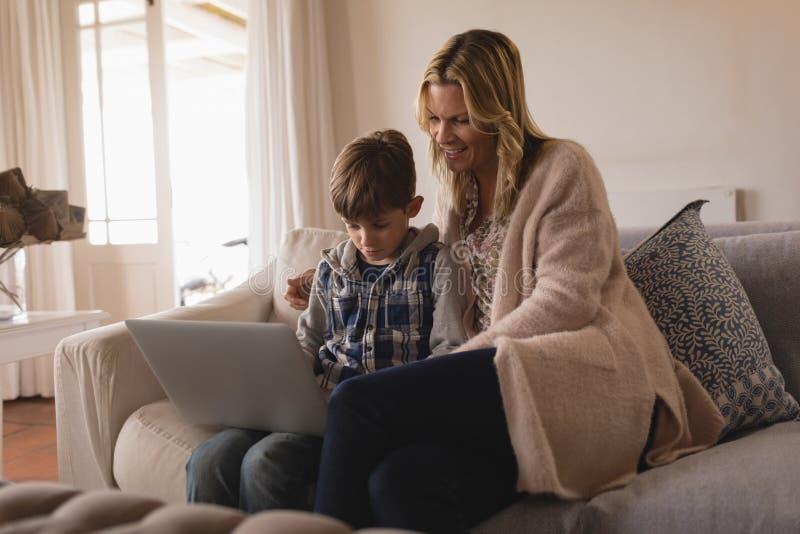 Mutter mit ihrem Sohn, der Laptop im Wohnzimmer verwendet stockbild