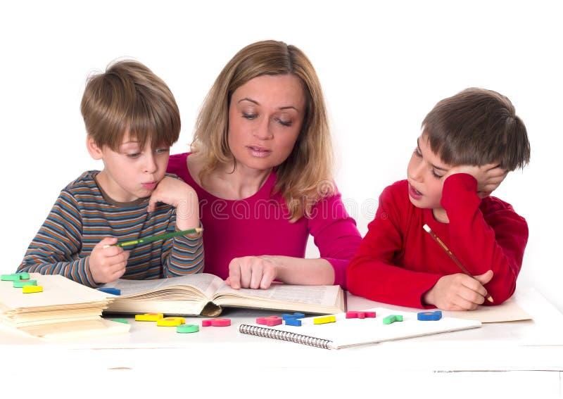 Mutter mit ihren Söhnen, ein Buch lesend lizenzfreie stockfotos