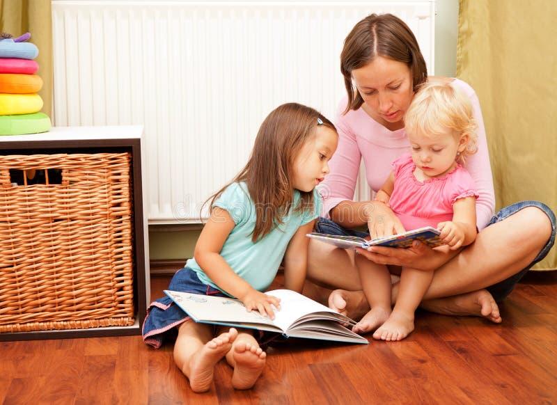 Mutter mit ihren Töchtern, die ein Buch lesen stockbild