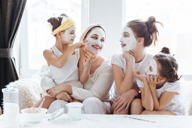 Mutter mit ihren Töchtern, die LehmGesichtsmaske machen stockbild