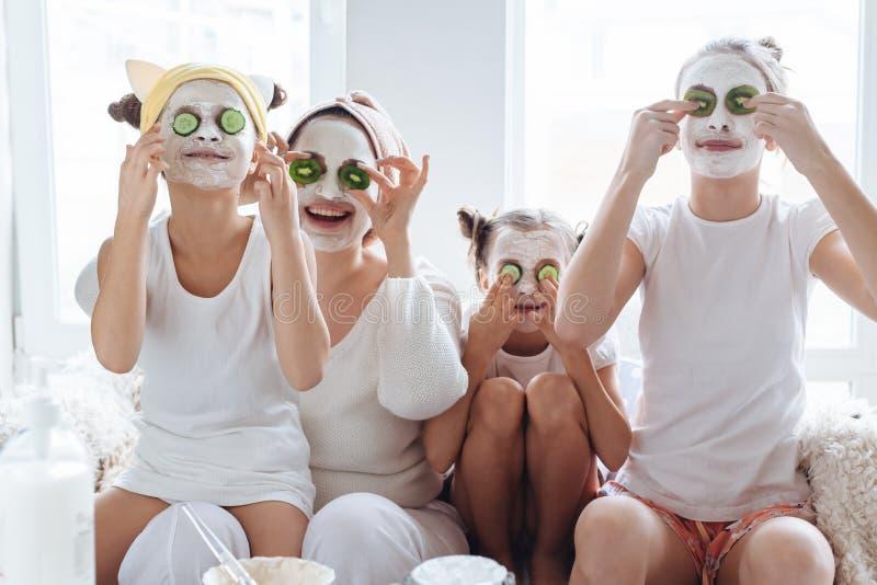 Mutter mit ihren Töchtern, die LehmGesichtsmaske machen lizenzfreies stockfoto
