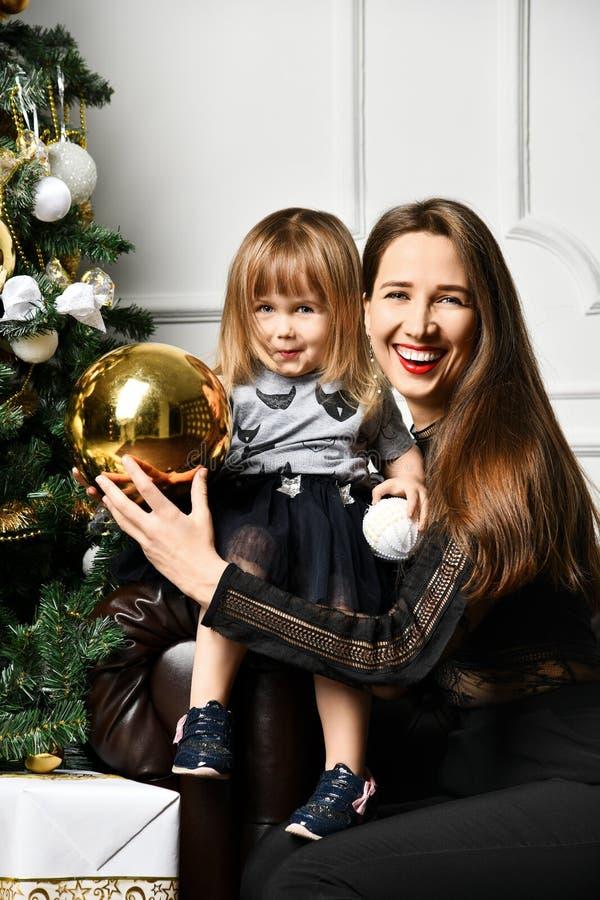 Mutter mit ihrer Kindertochter, die nahe Weihnachtsbaum feiert stockfotografie
