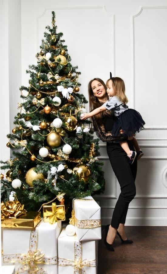 Mutter mit ihrer Kindertochter, die nahe Weihnachtsbaum feiert lizenzfreies stockfoto