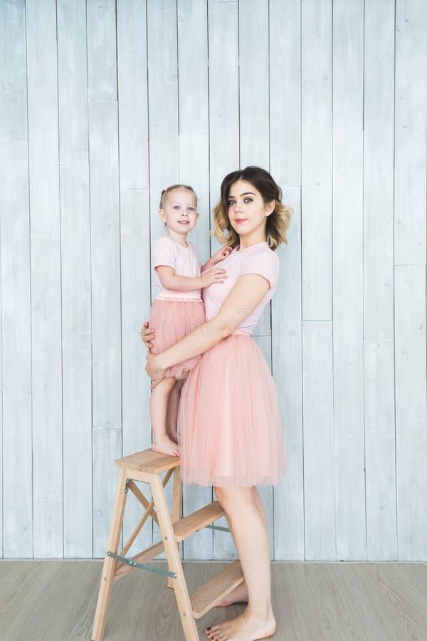 Mutter mit ihrer Tochter in der gleichen Kleidung auf einem weißen Hintergrund stockbild