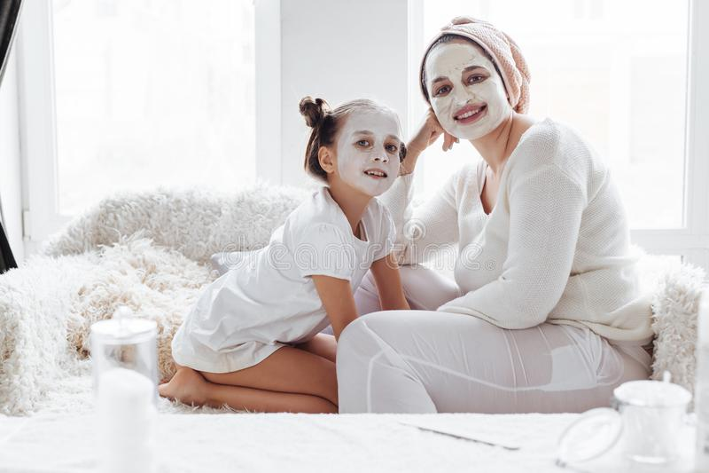 Mutter mit ihrer Tochter, die LehmGesichtsmaske macht lizenzfreie stockfotografie