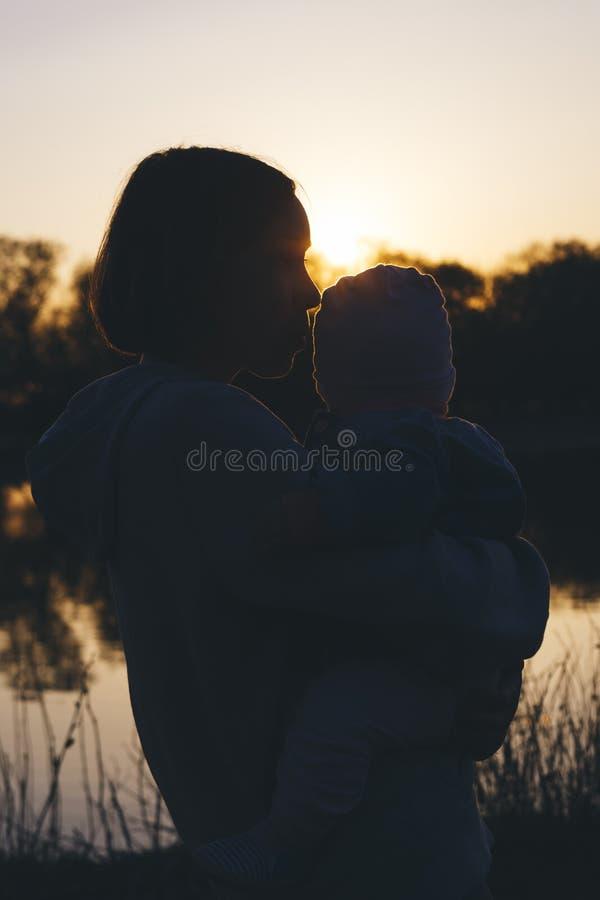 Mutter mit Kind bei Sonnenuntergang stockfotos