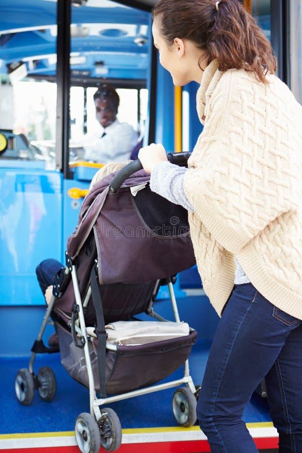 Mutter mit Kind im Kinderwagen-Einstieg-Bus stockbild