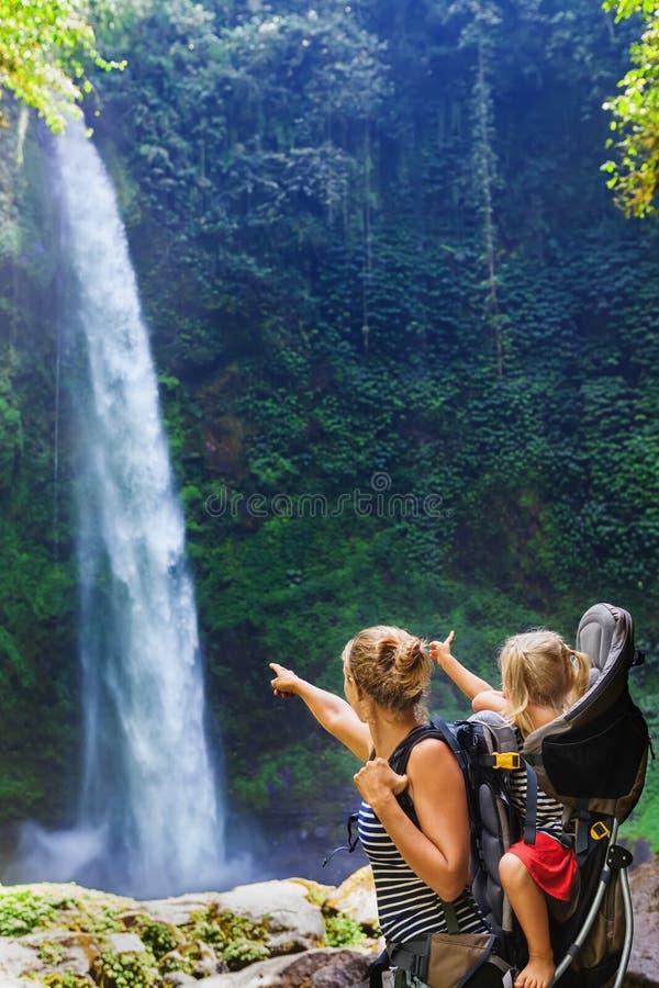 Mutter mit Kind im Rucksack, der Dschungelwasserfall betrachtet stockbilder