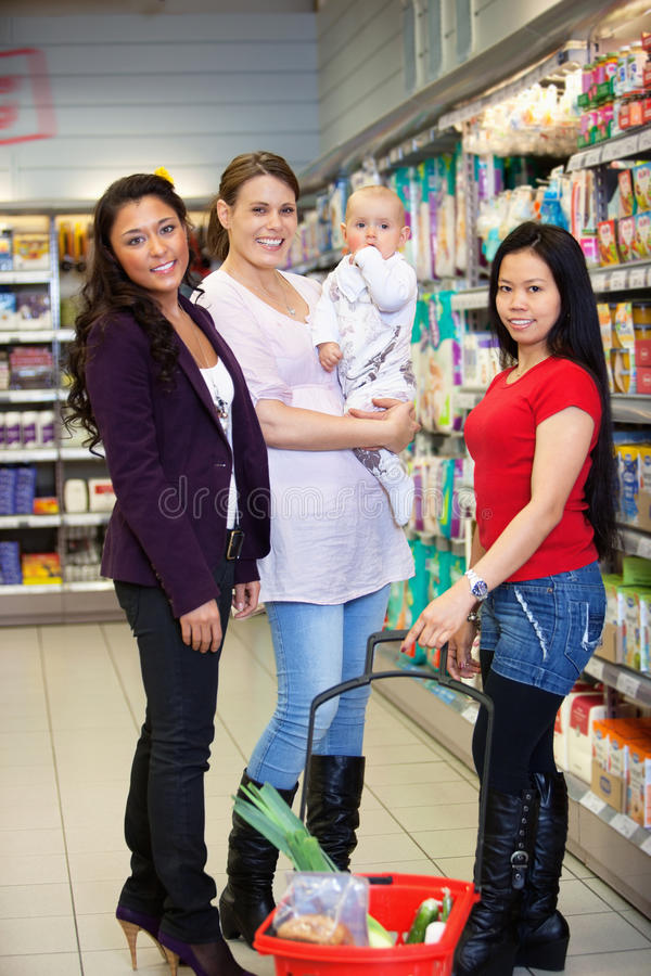 Mutter mit Kind und Freunden im Supermarkt lizenzfreies stockbild