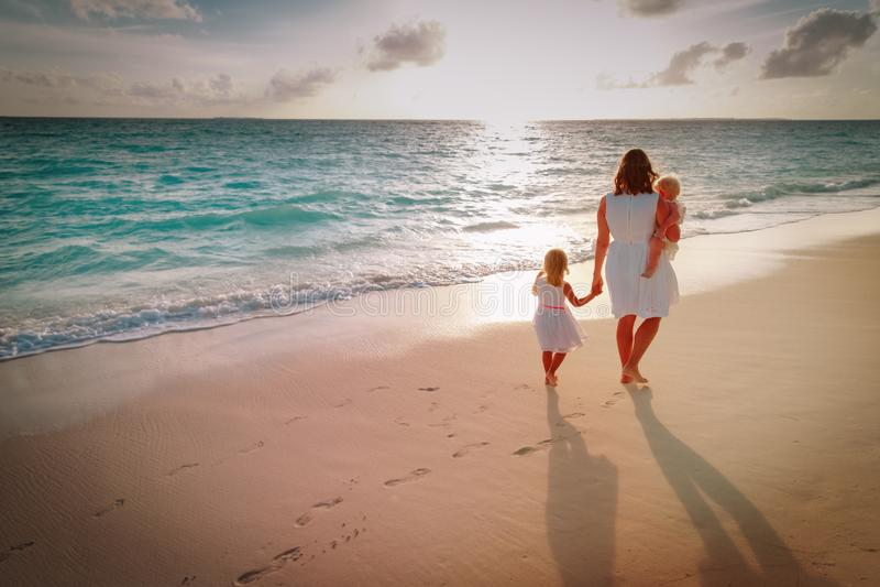 Mutter mit Kindern gehen auf Sandstrand stockfotos