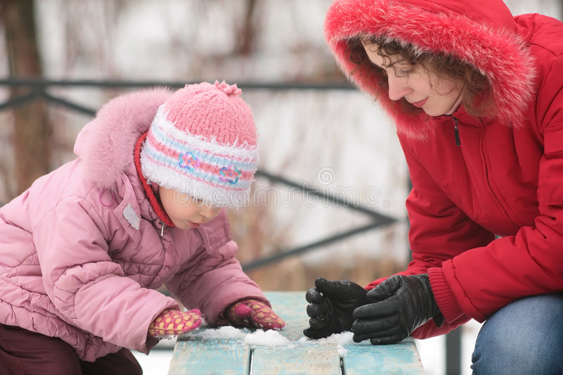 Mutter mit Kinderspiel mit Schnee auf Bank stockfotos