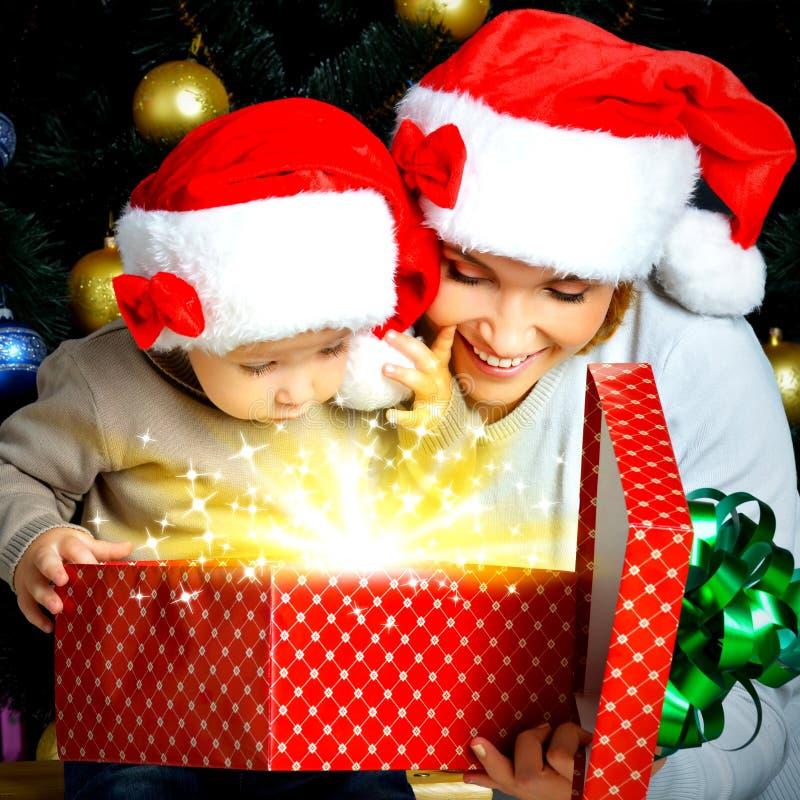 Mutter mit kleinem Kind öffnet den Kasten mit Geschenken auf Weihnachten lizenzfreies stockbild