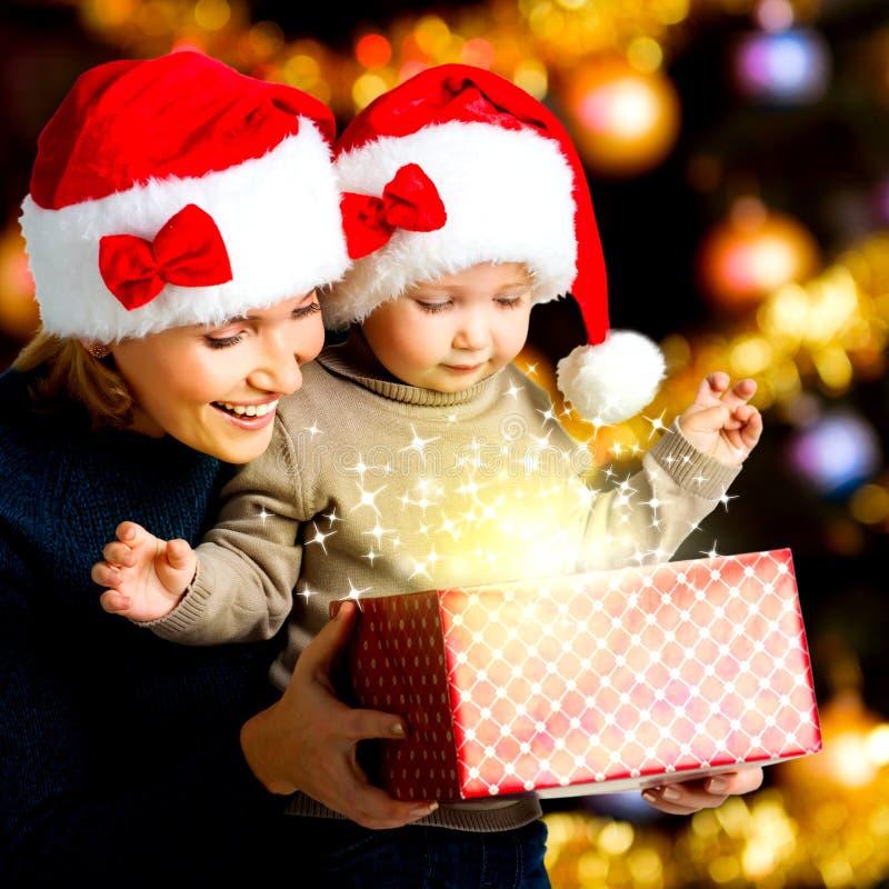 Mutter mit kleinem Kind öffnet den Kasten mit Geschenken auf Weihnachten stockfoto