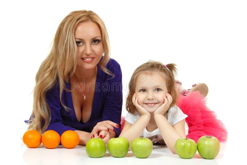 Mutter mit liitle Tochter mit Äpfeln und Orangen stockfotografie