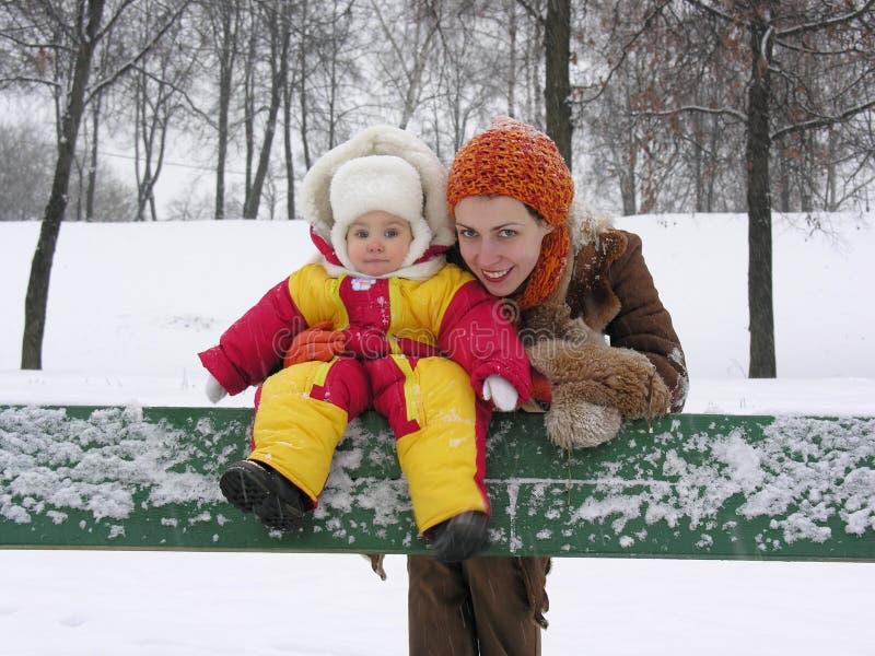 Mutter mit Schätzchen auf Bank. Winter lizenzfreies stockfoto