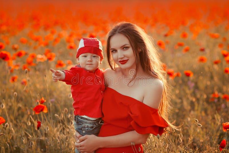 Mutter mit Sohn in den Mohnblumen, die das Leben bei Sonnenuntergang genießen Glückliche Familie lizenzfreie stockfotos