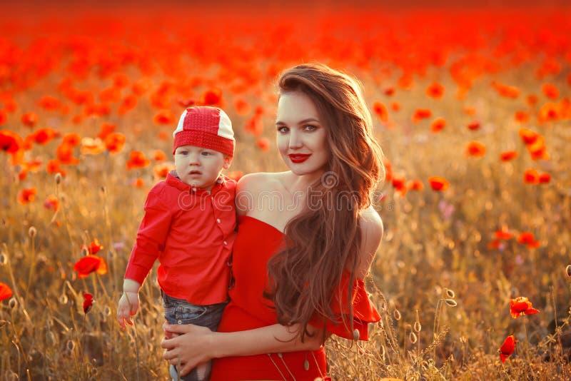 Mutter mit Sohn in den Mohnblumen, die das Leben bei Sonnenuntergang genießen Glückliche Familie lizenzfreies stockbild