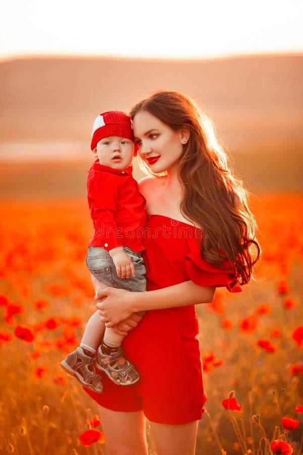 Mutter mit Sohn in den Mohnblumen, die das Leben bei Sonnenuntergang genießen Glückliche Familie stockfotos