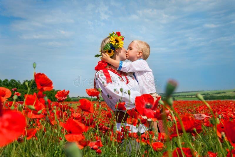 Mutter mit Sohn kleidete in Ukrainer gesticktem Kostüm auf dem roten Mohnblumenfeld Angebotkuß zu meiner Mutter an stockfotografie