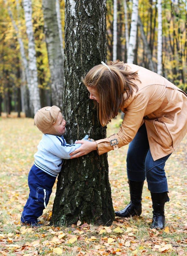 Mutter mit Sohnspielsuchvorgang und -fell lizenzfreie stockfotografie