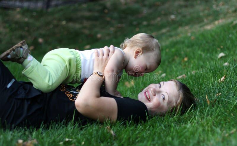Mutter mit sone Spiel auf einem Gras stockbilder