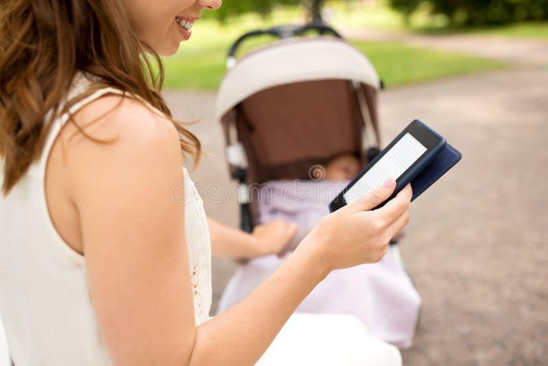 Mutter mit Spaziergängerleseinternet-Buch am Park lizenzfreies stockbild