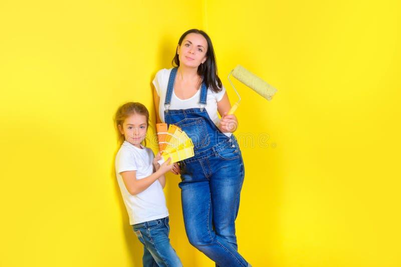 Mutter mit Tochter die Farbe für das Malen der Wand wählen stockfotos
