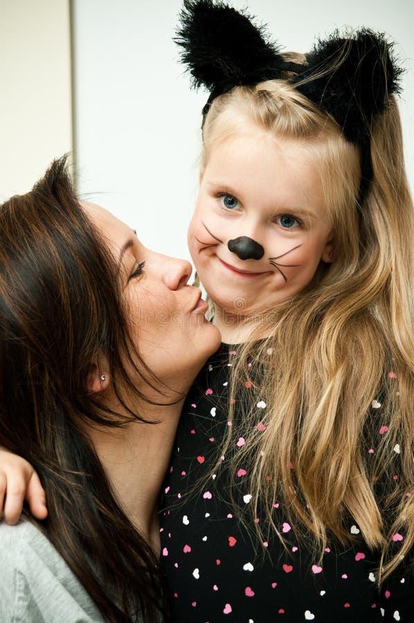 Mutter mit Tochter im Kätzchenkostüm stockbilder