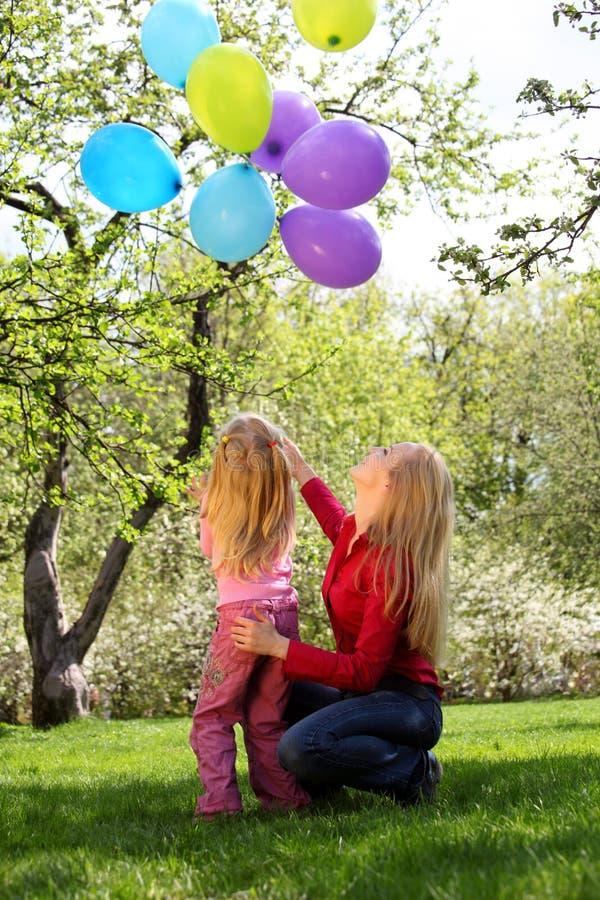 Mutter mit Tochter mit Garbe Ballonen stockfotos
