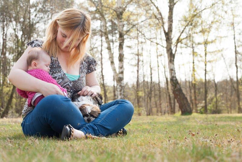 Mutter mit Welpen und Baby auf dem Gras stockfotos
