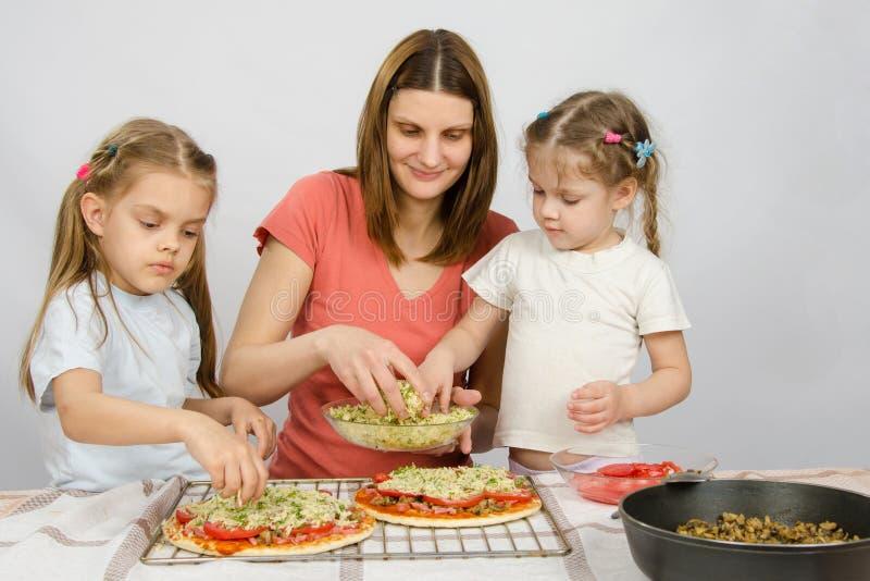 Mutter mit zwei Assistenten machen Pizza lizenzfreies stockfoto