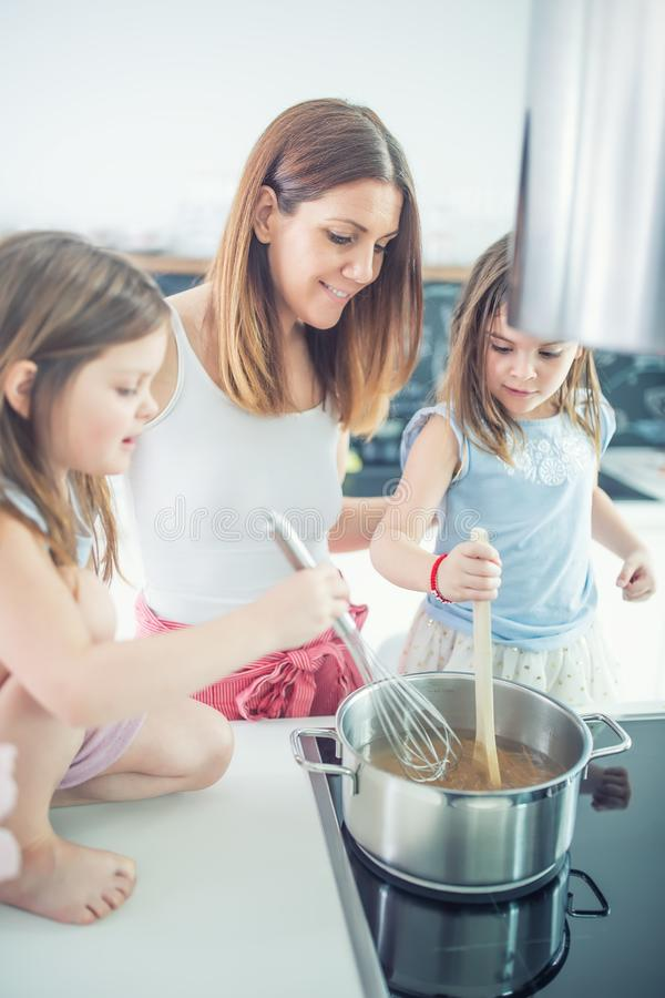Mutter mit zwei jungen Zwillingstöchtern in der Küche Spaghettis kochend lizenzfreie stockfotografie