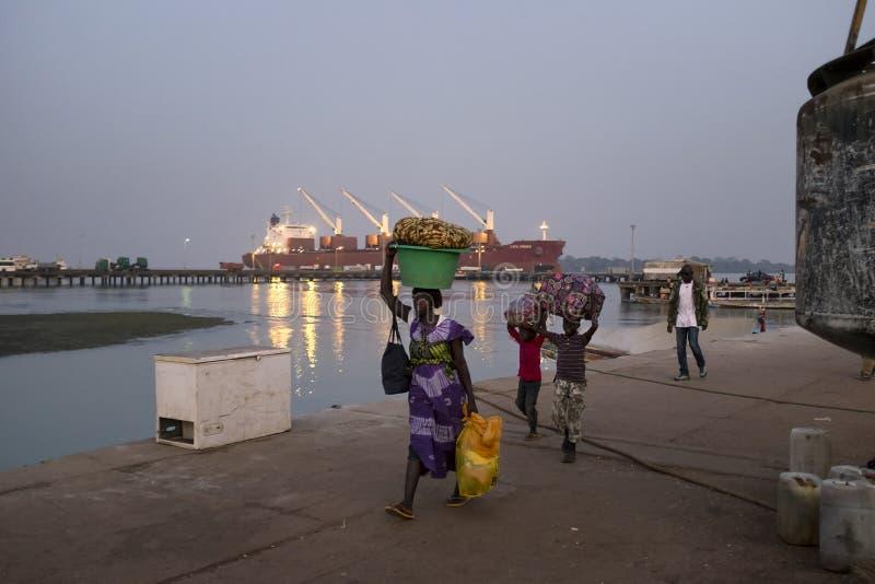 Mutter mit zwei Kindern, die im Hafen der Stadt Bissau in Guinea-Bissau ankommen stockfotos