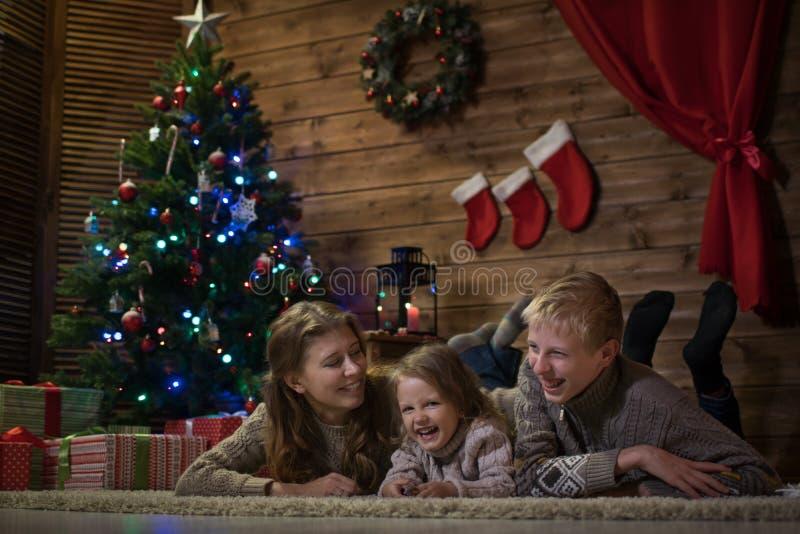 Mutter mit zwei Kindern nahe dem Weihnachtsbaum lizenzfreie stockfotos