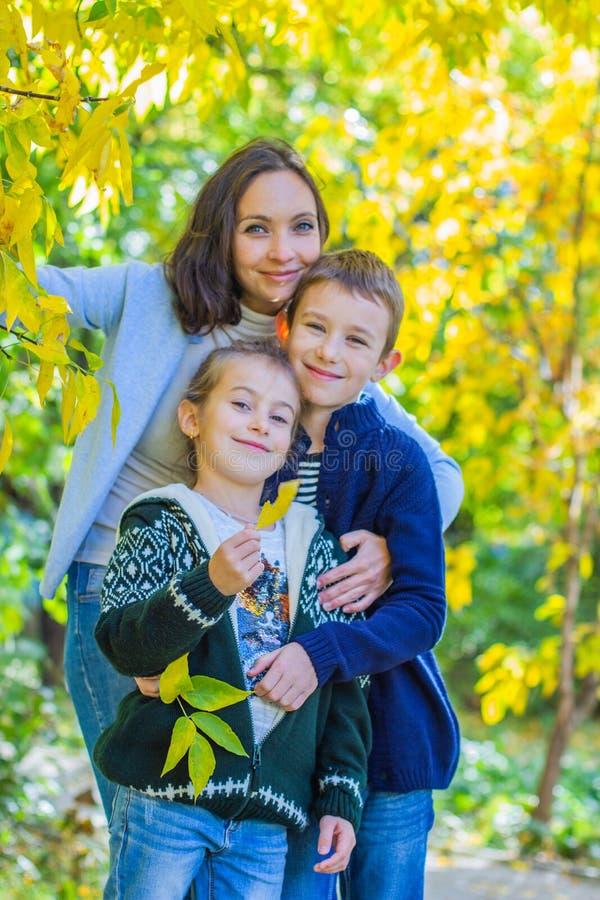 Mutter mit zwei Kindern unter dem Herbstbaumlächeln stockfoto