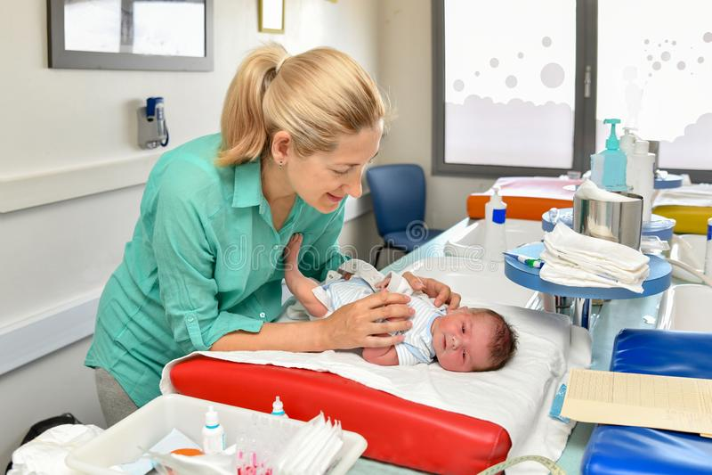 Mutter nehmen sich interessiert von ihrem neugeborenen Baby in der Geburtsklinik Erstes Bad lizenzfreies stockbild