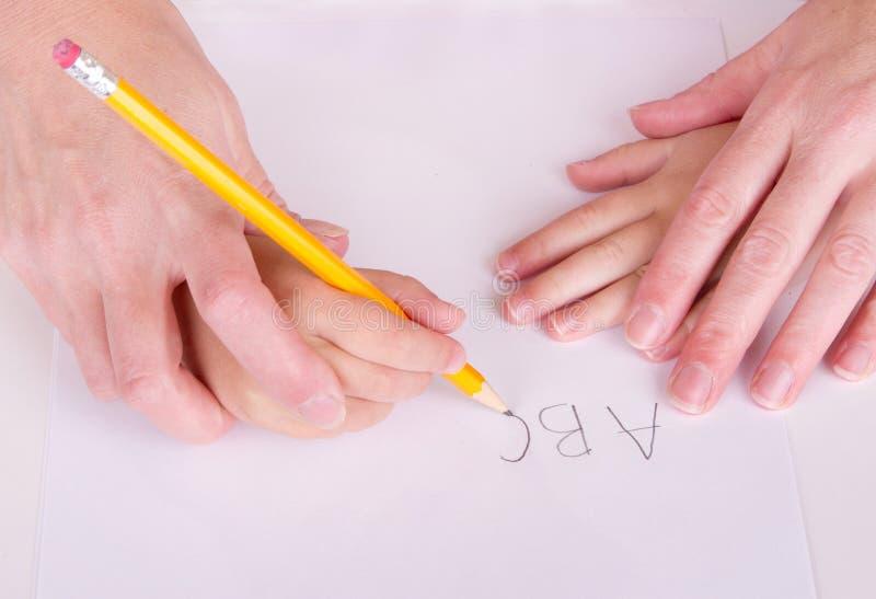 Mutter- oder des Lehrershelfendes Kind zum zu schreiben stockfotografie