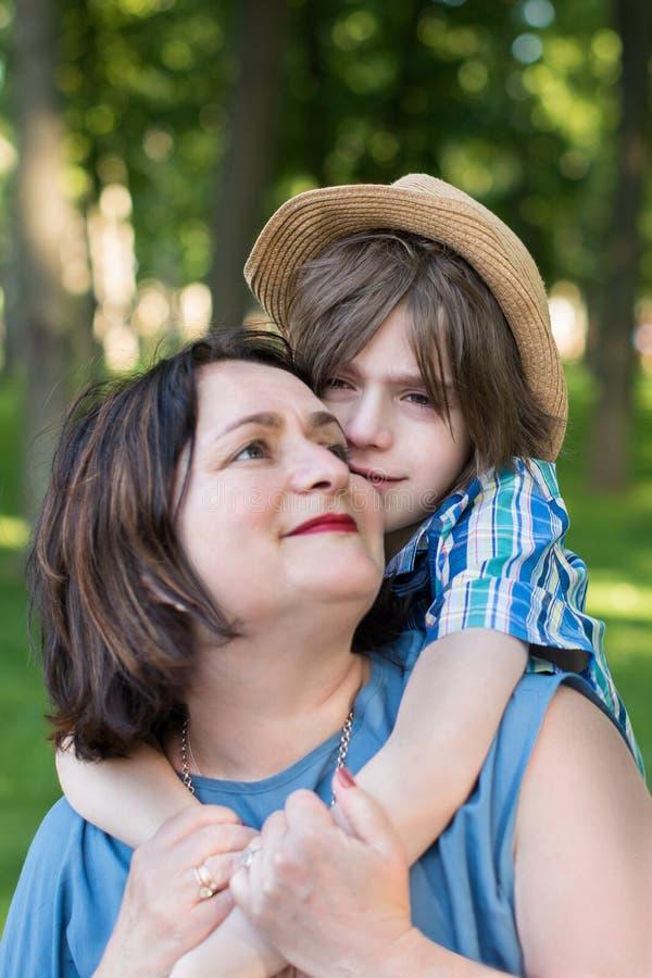 Mutter oder Großmutter beruhigt einen Sohn oder einen Enkel stockbild