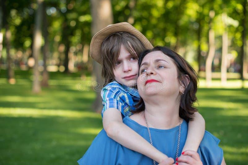 Mutter oder Großmutter beruhigt einen Sohn oder einen Enkel stockfotos