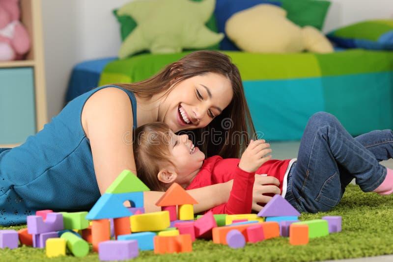 Mutter oder Kindermädchen, die mit einem Kind spielen stockfoto