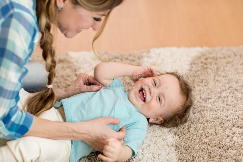 Mutter oder Kindermädchen, die zu Hause mit Kind auf Teppich im Raum spielen lizenzfreie stockfotos