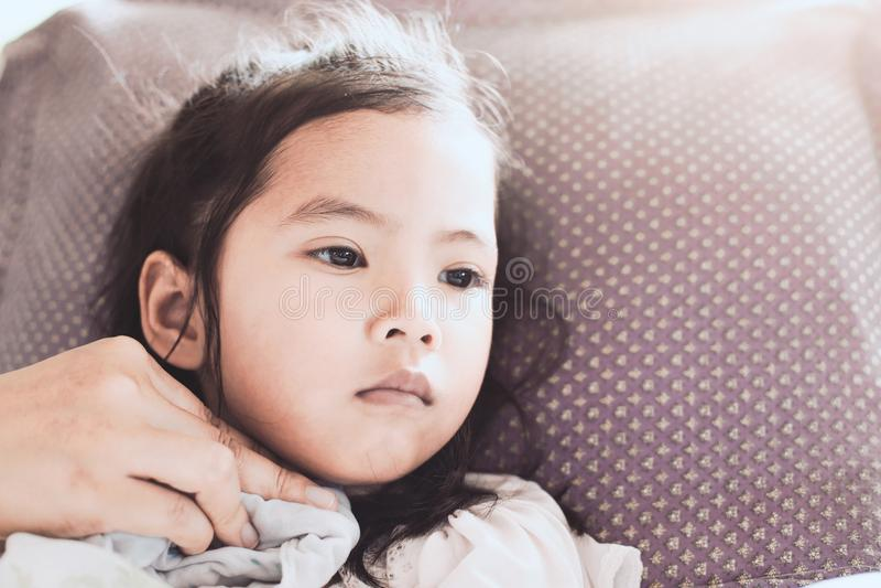 Mutter reibt den Körper des kranken asiatischen Kindermädchens stockfoto