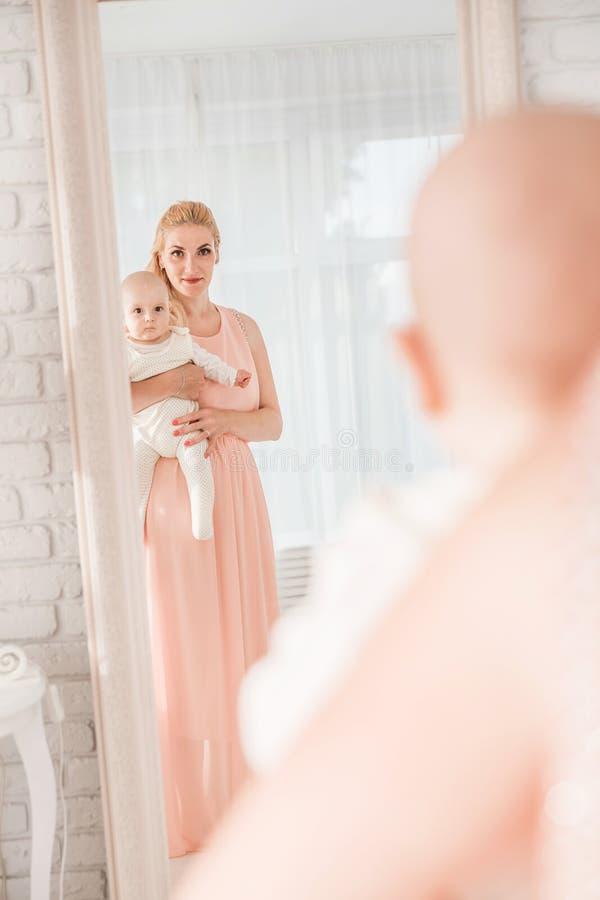 Mutter schaut mit ihrem Sohn im Spiegel stockfotografie