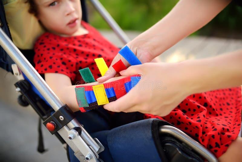 Mutter setzt Orthosis auf ihre Tochterarme Behindertes Mädchen, das auf einem Rollstuhl sitzt Kinderzerebralparese lizenzfreies stockbild